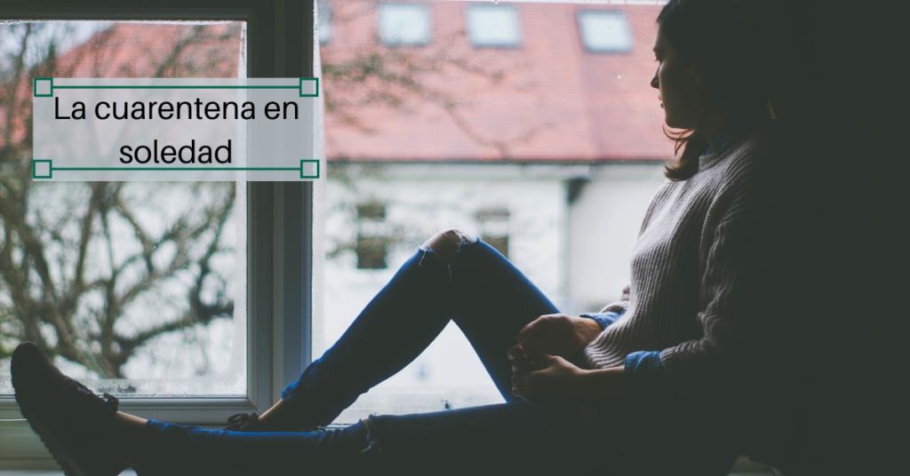 Una persona en soledad en su casa mirando por la ventana